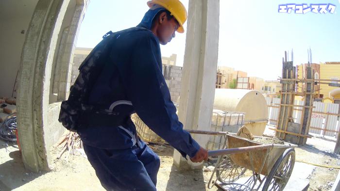二輪車で砂を運ぶ作業員 マスク