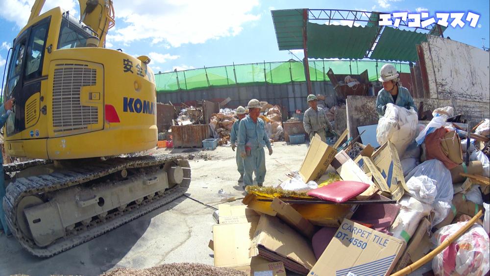 手作業で処理する。暑い 日本の産業廃棄物処理現場
